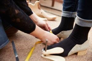 Schuhmacher beim Abmessen