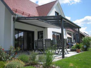 Terrassendächer Alu Bremen: Eine Überdachung mit Unterglasmarkise in Anthrazit mit vor Sonnenlicht geschütztn Gartenmöbel darunter.