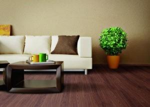 Vinylboden, einer der derzeit populärsten Bodenbeläöge, in dunkler Holzoptik verlegt im Wohnzimmer.