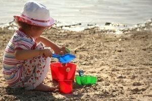 Sonnenschutz Bremen ein Kind am Strand mit Hut