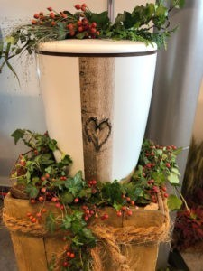 Bestattungsvorsorge: Weiße Urne mit einel Holzelement und schwarzem Herz darauf umrandet von grünen Zweigen.