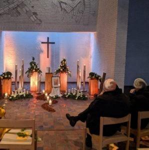 Trauerfeuer in einer christlich aufgemachten Trauerhalle. An der Wand hängt ein Kreuzt, es sind Kerzen angerichtet und ein Bild des Verstorbenen aufgestellt. Zwei Menschen sitzen auf Stühlen in der ersten Reihe.